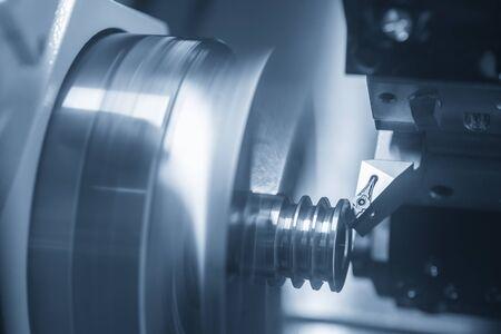 Die CNC-Drehmaschine schneidet den Schlitz an den Metallteilen. Der Herstellungsprozess von Automobilteilen durch Drehmaschine.