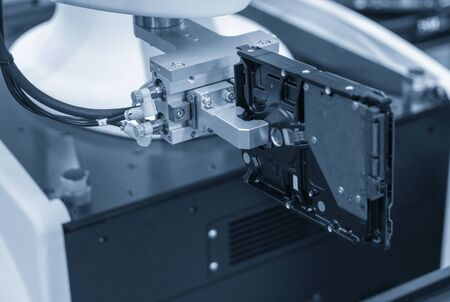 The robotics system handing the hard disk parts on assembly line. The hi-technology computer parts manufacturing process.