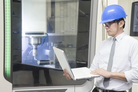 The engineer control the CNC milling machine by notebook. The machining center operation by engineer control processing.