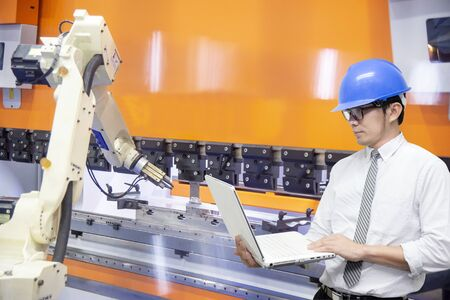 The engineer programming the robotic arms for loading the sheet metal to the hydraulic bending machine. The hi-technology in sheet metal working manufacturing process by autonomous robotic system.
