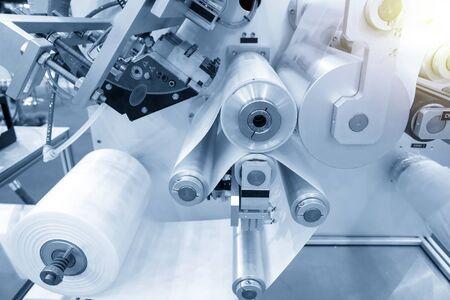 Il funzionamento della macchina per la produzione automatica di sacchetti di plastica con effetto luminoso. Primo piano del rullo della macchina per la produzione di sacchetti di plastica nella scena blu chiaro. Archivio Fotografico