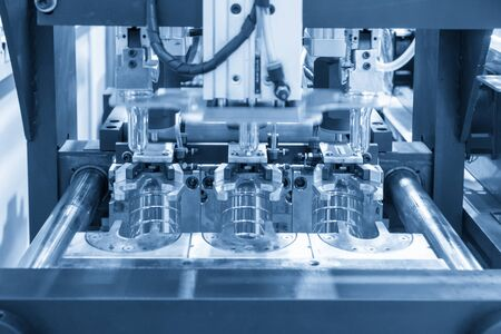 The blowing mould operation of PET bottles drinking water container manufacturing processing in the light blue scene. The plastic drinking water bottle manufacturing processing by blow mould machine. 写真素材
