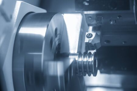 The CNC lathe machine groove cutting on the metal pulley parts with lathe cutting tools. The hi-technology parts production process by turning process in the light blue scene. Stock Photo