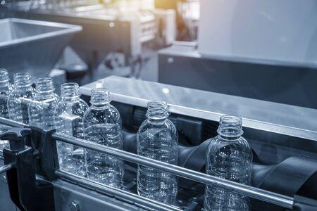 De PET-flessen op de transportband voor het vulproces in de drinkwaterfabriek. Het productieproces van de drinkwaterfabriek door automatische vulmachine in de fabriek.