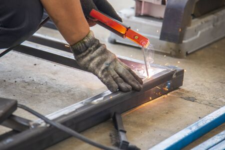 The skill worker use the electric welding machine welding the metal tube structure for assembly  the metal frame. The construction worker build the metal frame by electric welding machine.