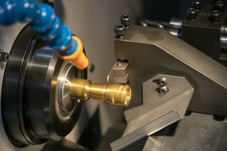 The multi-tasking CNC machine slot cutting at the brass shaft parts with the slot  tool. The hi precision  parts manufacturing process by CNC lathe machine with the cutting tools. Stock Photo