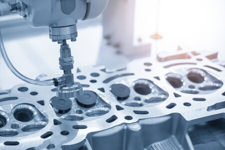 The aluminium casting cylinder head parts in the assembly process with the exhaust and intake valve parts in the light blue scene. The robotic arm system in automotive parts manufacturing process .