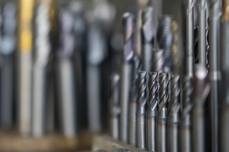 The various type cutting tools of CNC machine on the stock shelf in the light blue scene. The collection of CNC cutting tool , solid ball ,bull or radius ,flat or square, tapping endmill tools.