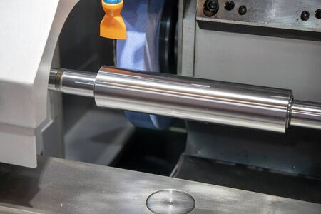 The cylindrical grinding machine make the surface finishing on the metal shaft control by CNC program. The metal working processing on the cylindrical surface grinding machine. Stock Photo - 132016199