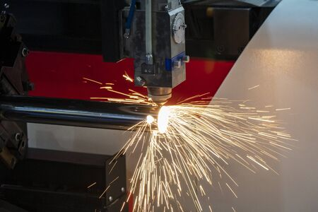 The fiber laser cutting machine cutting the stainless steel tube control by CNC program. The sheet metal working processing by laser cutting machine make the engrave at the stainless steel pipe parts. Banco de Imagens