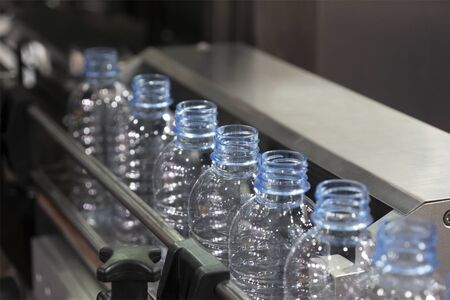 The PET bottles on the conveyor belt for filling process in the drinking water factory. The drinking water factory production process by automatic filling machine in the plant. Stok Fotoğraf - 132015848