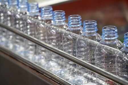 The PET bottles on the conveyor belt for filling process in the drinking water factory. The drinking water factory production process by automatic filling machine in the plant.