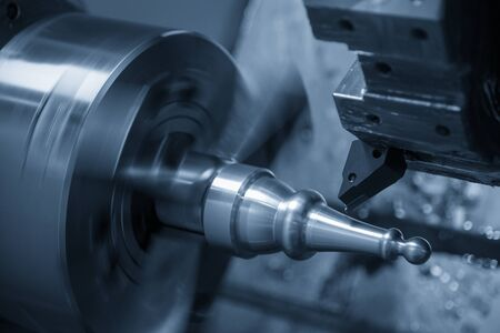The CNC lathe machine in metal working process cutting the metal shaft parts with the cutting tools. The automotive parts production processing by CNC turning machine . Stock fotó - 133247245