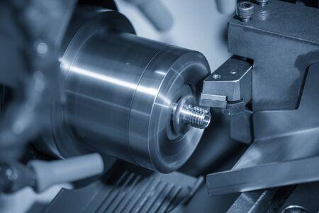 Die CNC-Drehmaschine im Metallbearbeitungsprozess schneidet die Schraubenteile mit den Schneidwerkzeugen. Die Herstellung von Automobilteilen durch CNC-Drehmaschine. Standard-Bild