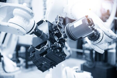 The automotive parts finishing process by milling spindle attach at the robotic arm. The aluminium casting gearbox parts machining process by automatic robotic system attach the milling spindle . Stockfoto