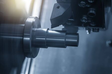 The CNC lathe machine in metal working process cutting the metal shaft parts with the cutting tools. The automotive parts production processing by CNC turning machine . Stock Photo