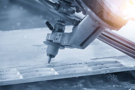 The abrasive multi-axis  water jet machine cutting the aluminium plate with lighting effect. The hi-technology sheet metal working production line by  water jet machine control by CNC program. Stock Photo