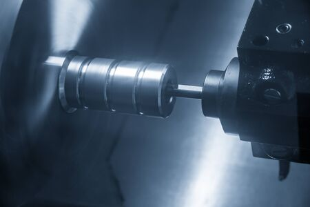 The CNC lathe machine in metal working process bore cutting the metal shaft parts with the cutting tools. The high precision parts production processing by CNC turning machine . Stock Photo