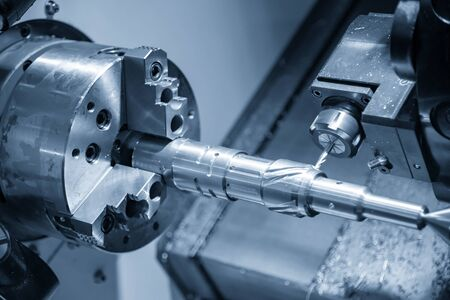 The multi-tasking CNC lathe machine cutting the automotive parts by  milling spindle  with the cutting tools. The automotive parts production processing by CNC turning machine . Stock Photo
