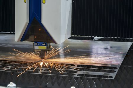 The fiber laser cutting machine control by CNC program system. The hi-technology sheet metal manufacturing process by laser cutting machine. 版權商用圖片