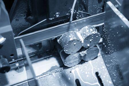 Le fonctionnement de la scie à ruban coupant la tige métallique. La préparation du matériau du lingot pour le processus d'usinage par une scie à ruban automatique.