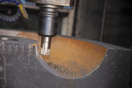 La fresadora CNC corta en bruto las piezas del molde de hierro fundido con una herramienta de fresa de radio indexable. El proceso de fabricación de piezas de molde de hierro fundido por centro de mecanizado. Foto de archivo