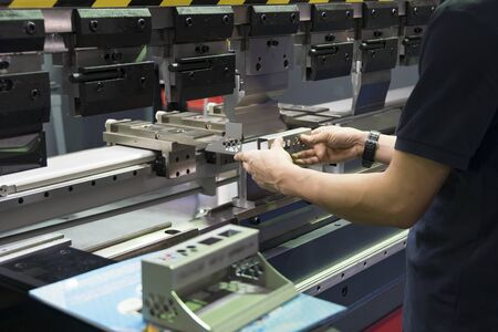 Operation of press brake hydraulic bending machine with forming die by skill operator. The sheet metal manufacturing process by bending machine with technician operator. Stockfoto