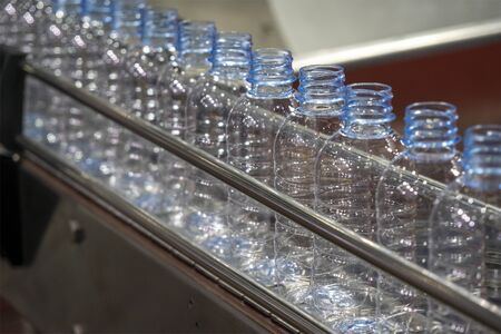Les bouteilles PET dans le rail sur la bande transporteuse pour le processus de remplissage dans l'usine d'eau potable. Le processus de production d'usine d'eau potable par machine de remplissage automatique dans l'usine. Banque d'images