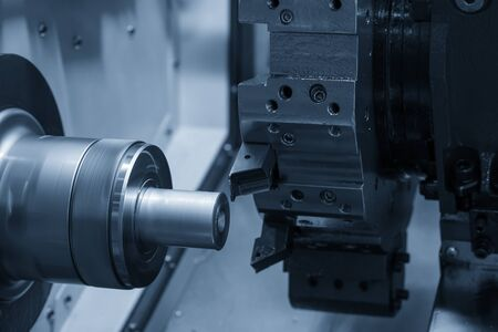 The CNC lathe machine in metal working process cutting the metal shaft parts with in the light blue scene. The hi-technology metal working processing by CNC turning machine .
