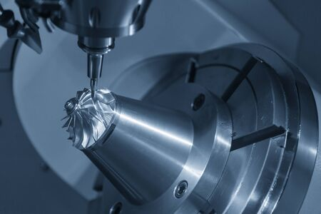The 5-axis CNC milling machine cutting the aluminium turbine propeller part by solid ball endmill tools. The turbocharger parts manufacturing process by 5-axis machining center. Stock Photo