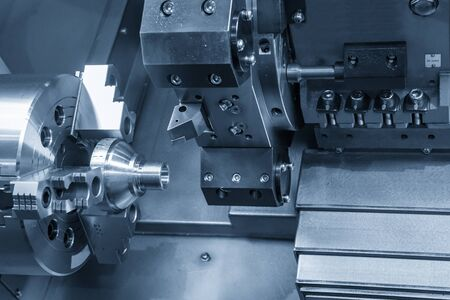 The CNC lathe machine in metal working process cutting thread the at the end of metal cone shape parts in the light blue scene. The hi-technology metal working processing by CNC turning machine .