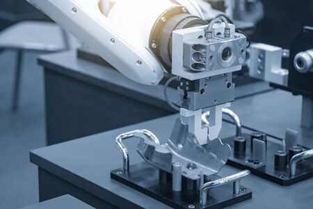 The robotic arm gripping the formed sheet metal parts from the setting jig to the conveyor belt in automotive factory. The hi-technology material handing process in by robotics system. Foto de archivo