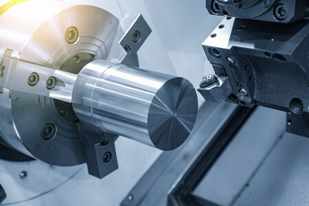 The CNC lathe machine rough cutting the metal shaft parts with lighting effect. The hi-technology metal working processing by CNC turning machine . Foto de archivo