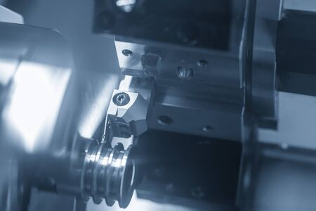 The CNC lathe machine groove cutting the metal pulley parts with lighting effect. The hi-technology metal working processing by CNC turning machine .