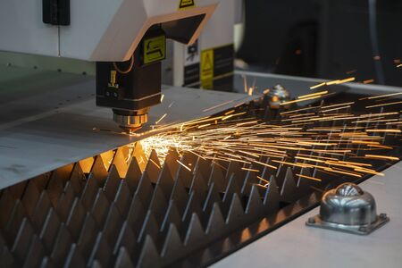 The fiber laser cutting machine cutting the sheet metal  plate with the sparkling light.  The hi-technology sheet metal manufacturing process by laser cutting machine.