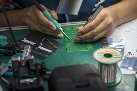 The skill operator soldering the PCB board . The manual soldering operation in electronics industry manufacturing process.