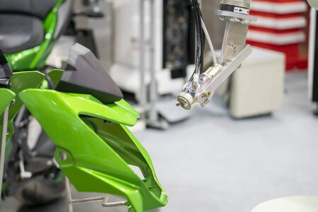 The painting robot spray the green color to the motorcycle mask parts. The automatic automotive parts painting system by robotics system.