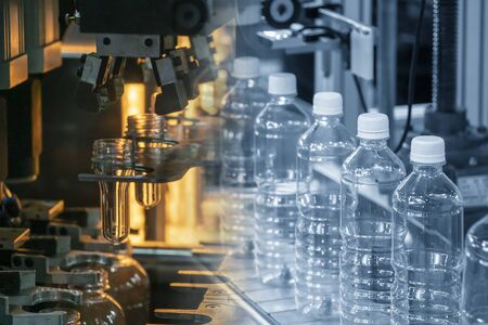 The abstract scene of tube preform shape of bottles preheat process and the plastic bottle in the conveyor belt. The PET bottle manufacturing processing.