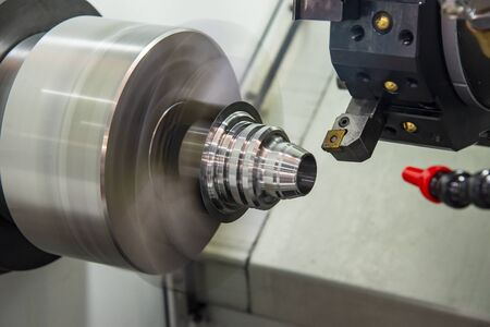 The CNC lathe machine finish cutting the metal cone shape parts with cutting tools. The hi-technology metal working processing by CNC turning machine .