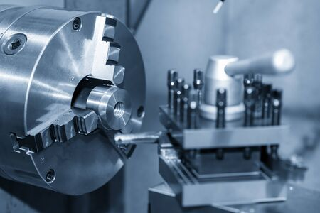 The operation of lathe machine cutting the metal parts with the cutting tools. The metalworking process by turning machine. Stock Photo