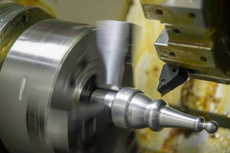 The CNC lathe machine finish cut the metal shaft parts. The hi-technology metal working processing by CNC turning machine .
