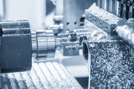 The  multi-tasking CNC lathe machine swiss type drilling at the brass  shaft . The hi-technology metal working process with turning machine control by CNC program