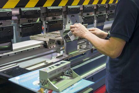 The operation of hydraulic bending machine with technician.  The automotive sheet metal manufacturing process by bending machine with technician operator. Zdjęcie Seryjne