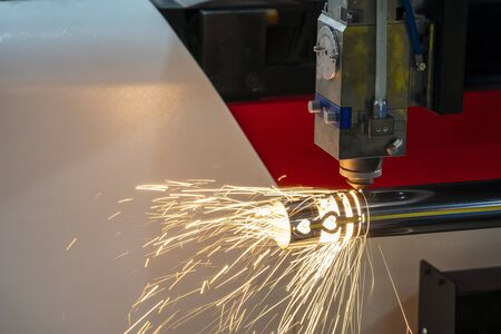 The fiber laser cutting machine cutting the stainless steel tube control by CNC program. The sheet metal working processing by laser cutting machine make the engrave at the stainless steel pipe parts. Zdjęcie Seryjne