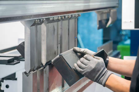 The metalworking operator working with hydraulic bending machine. The automotive sheet metal manufacturing process by bending machine with technician operator.
