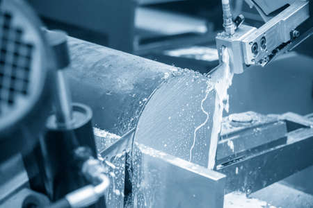 The automatic band saw machine cutting the metal rod with the liquid coolant. The machine tool operation with liquid coolant.