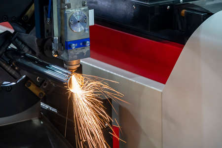 The fiber laser cutting machine cutting the stainless steel tube control by CNC program. The sheet metal working processing by laser cutting machine make the engrave at the stainless steel pipe parts. Фото со стока