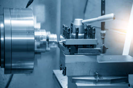 The operation of lathe machine cutting the brass shaft parts with the cutting tools. The metalworking process by turning machine. Фото со стока