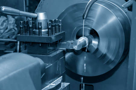 The operation of lathe machine cutting the metal shaft parts with the cutting tools. The metalworking process by turning machine. Banco de Imagens