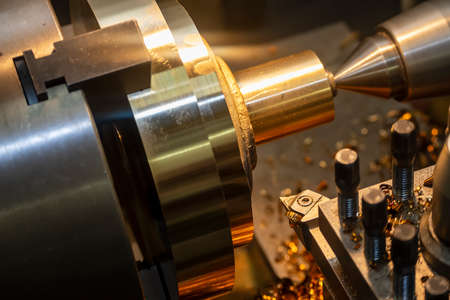 The operation of lathe machine cutting the brass  shaft parts with the cutting tools. The metalworking process by turning machine.